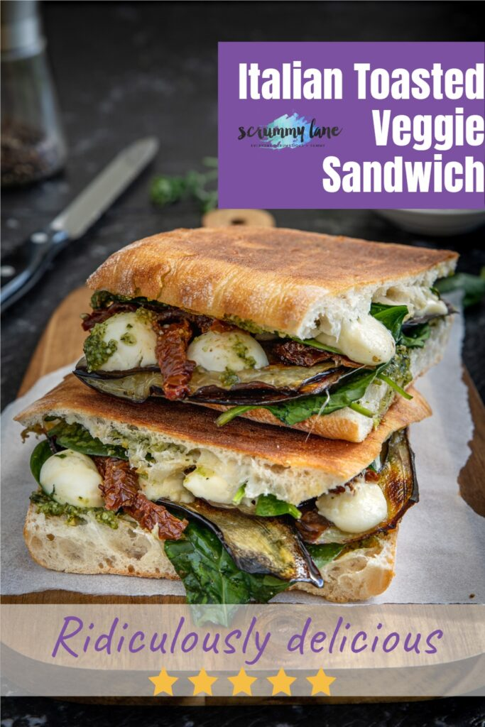 Two halves of an Italian toasted veggie sandwich on a wooden board for Pinterest with a title on it