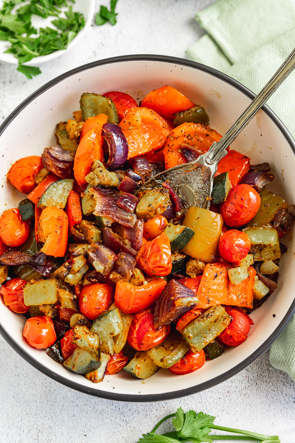 A dish of Mediterranean roast vegetables from above with a spoon in it on a white background and with a green tea towel