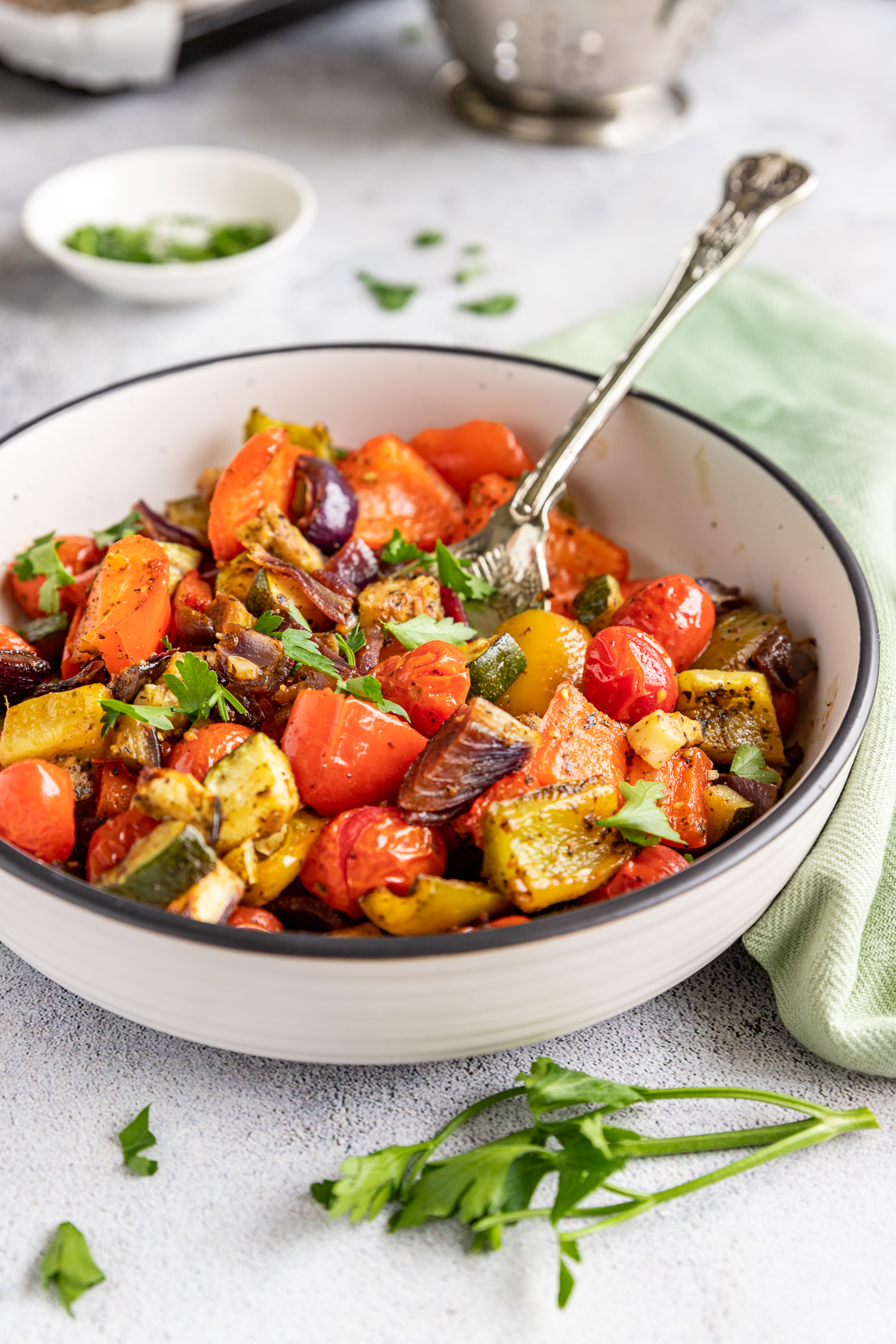 A white dish of Mediterranean roast vegetables on a pale background, with a decorative spoon in it and with a green tea towel and herbs in the background