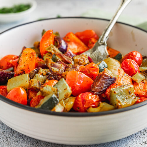 A dish of Mediterranean roast vegetables on a white background with a spoon in it and a green tea towel in the background