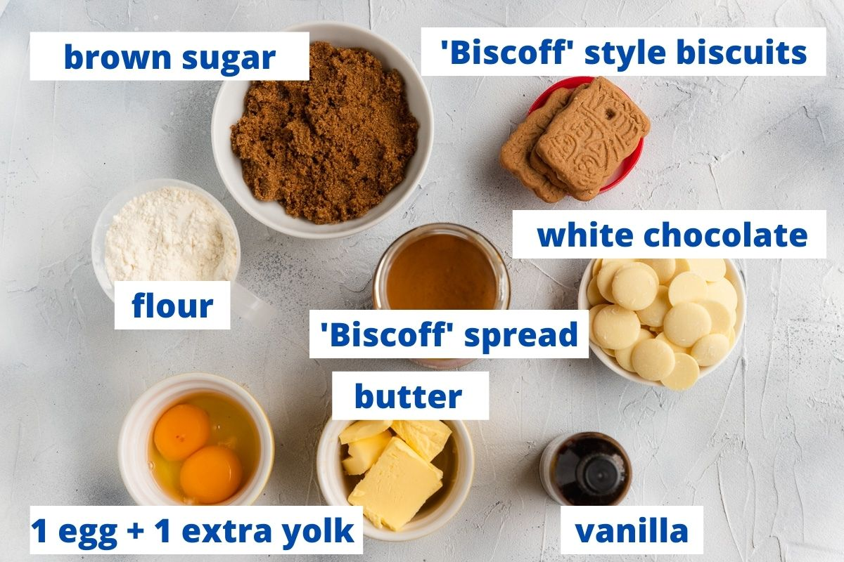 All the ingredients needed to make Biscoff blondies, labelled including brown sugar, Biscoff biscuits, flour, white chocolate, Biscoff spread, butter, eggs and vanilla
