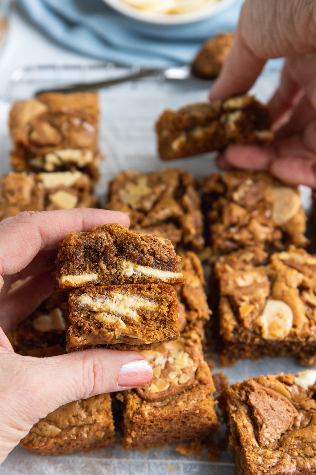 Someone holding a stack of two Biscoff blondies over the others in the pan with someone else taking a blondie in the background