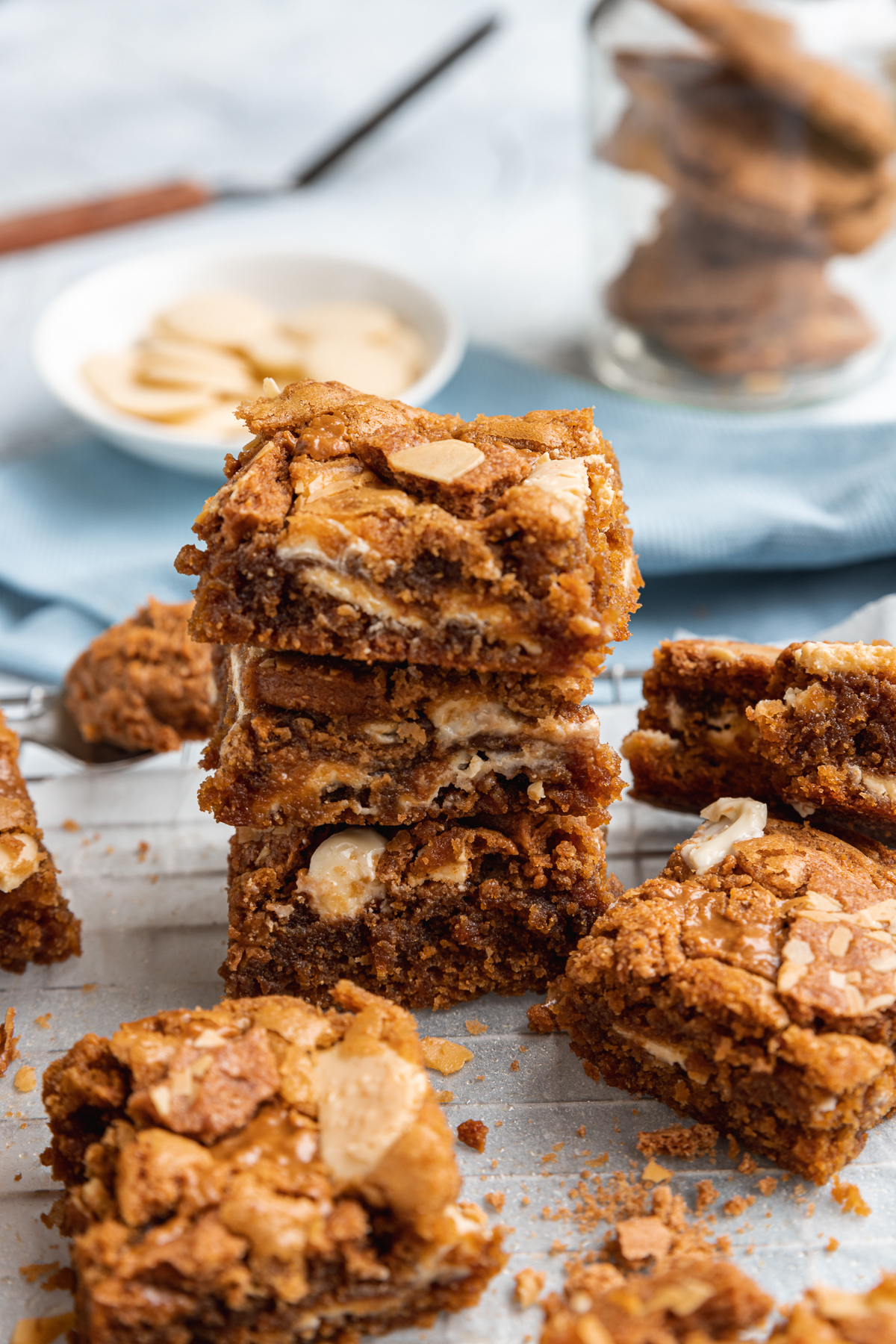 A stack of 3 Biscoff blondies on a wire cooking rack with ingredients in the background and other blondies all around