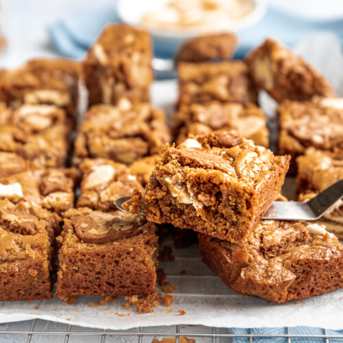 Biscoff blondies just out of the pan on baking paper and a cooling rack and with ingredients in the background