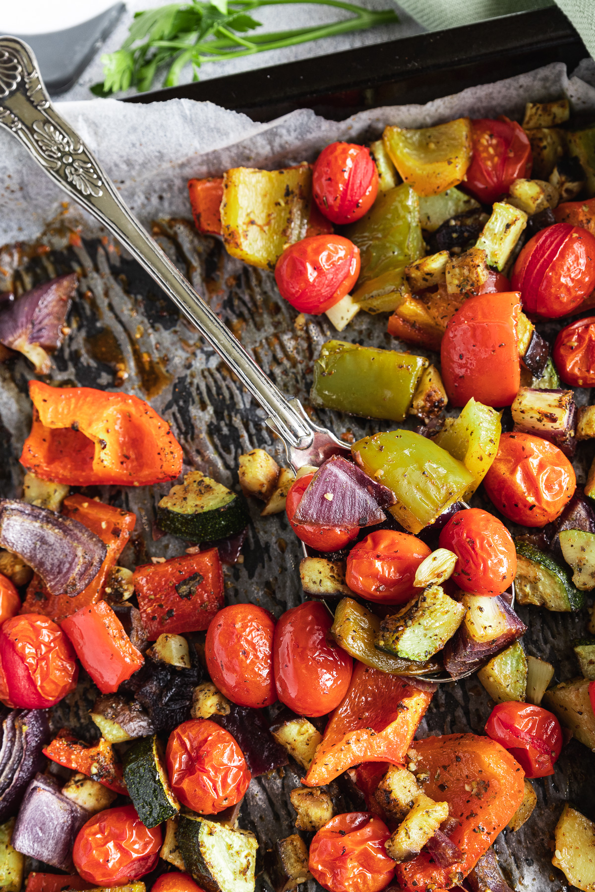 Closeup of baking tray of Mediterranean roast vegetables with a spoon in it