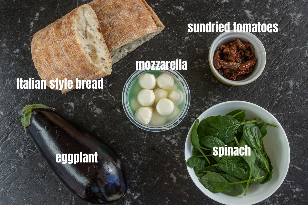 Pictures of the ingredients needed to make an Italian veggie sandwich: eggplant, Italian style bread, mozzarella balls, sundried tomatoes, spinach