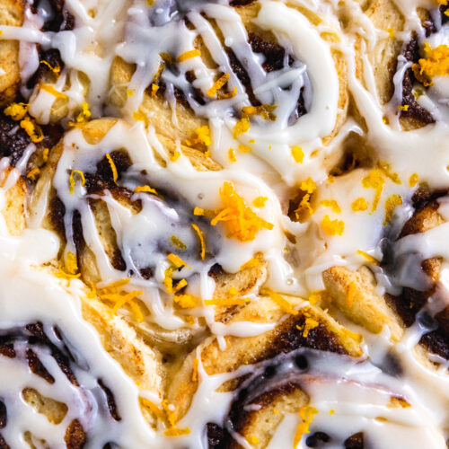 A closeup of cinnamon rolls from above drizzled with icing and orange zest