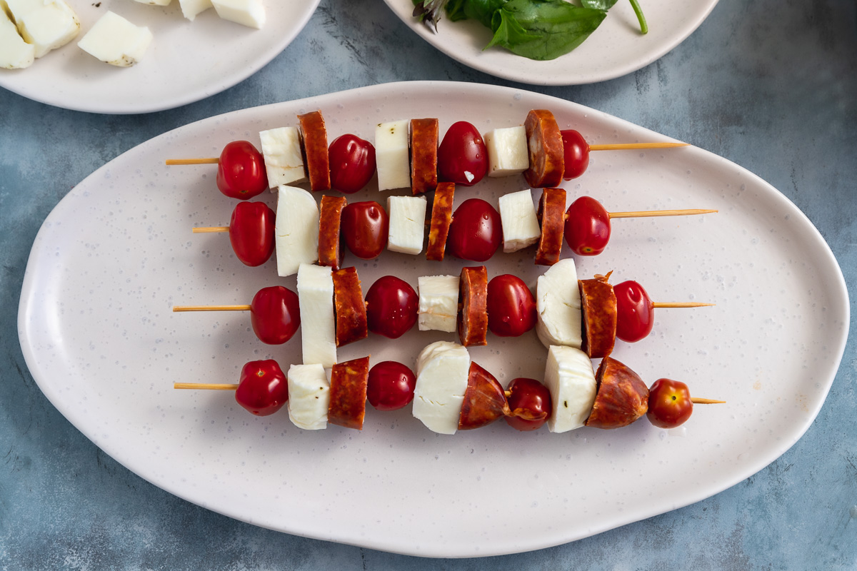 4 halloumi skewers on an oval platter before they're cooked
