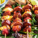 A closeup of 4 halloumi kebabs on a white platter and on a bed of green leaves with bread and lime segments on the side