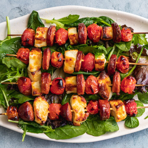 A platter of halloumi kebabs with chorizo and tomatoes from above on a blue-grey background
