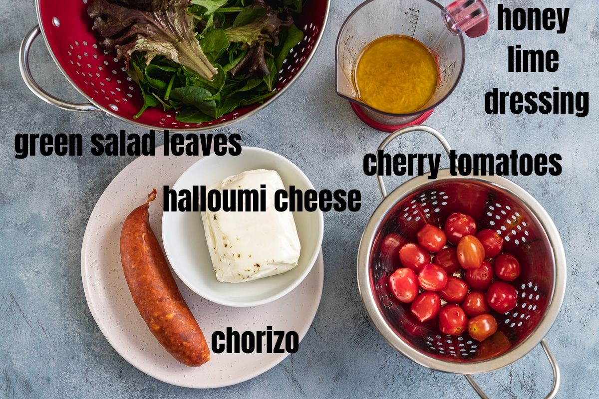 All the ingredients you need to make halloumi kebabs with chorizo and tomatoes including green salad leaves, honey lime dressing, halloumi cheese log, chorizo sausage and cherry tomatoes