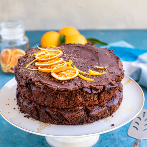 A finished chocolate orange cake decorated with orange slices on a white cake stand and on a blue background with a grey wall and ingredients behind