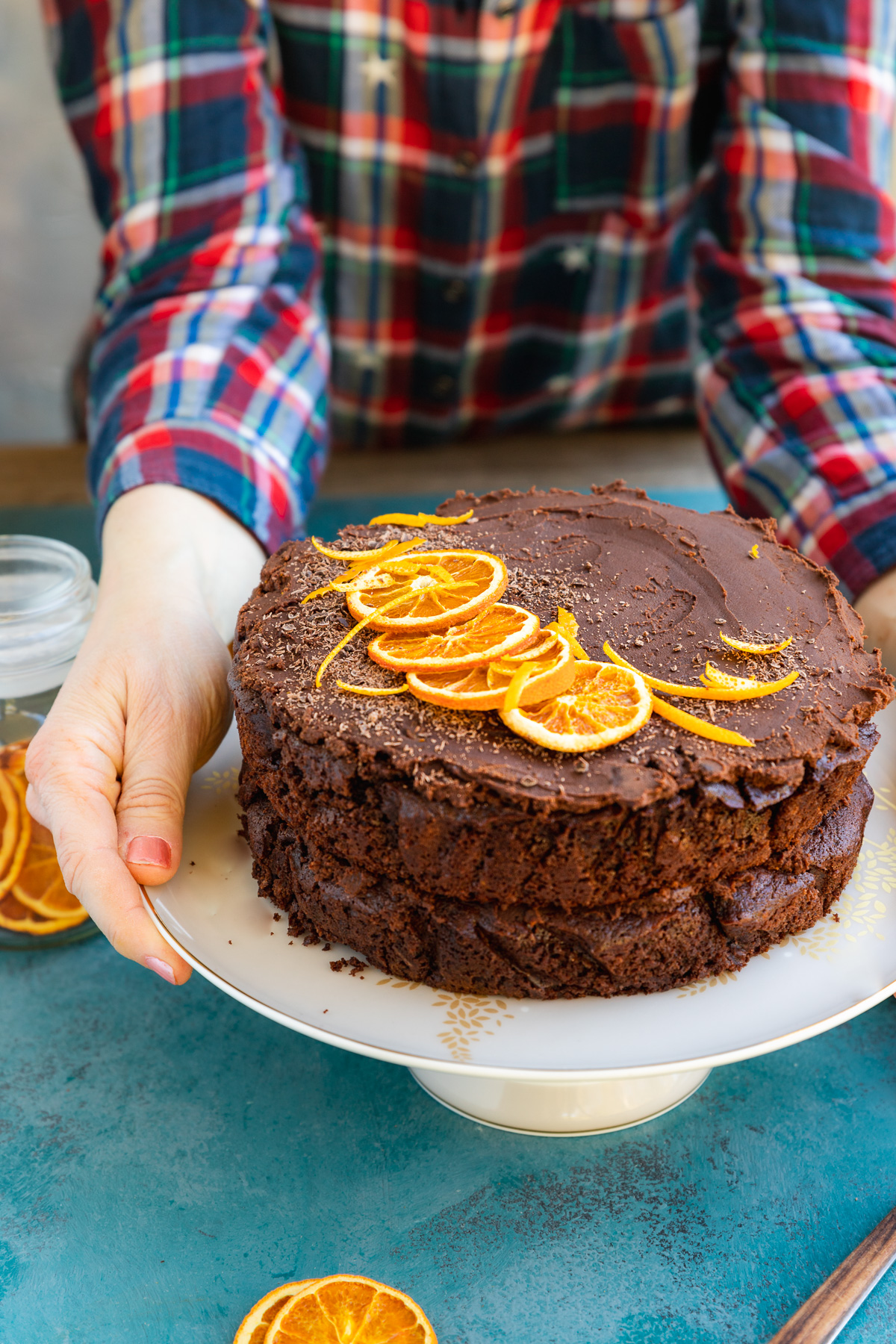 Someone in a red and blue checked shirt placing a decorated chocolate orange layer cake on a white cake stand on a blue surface
