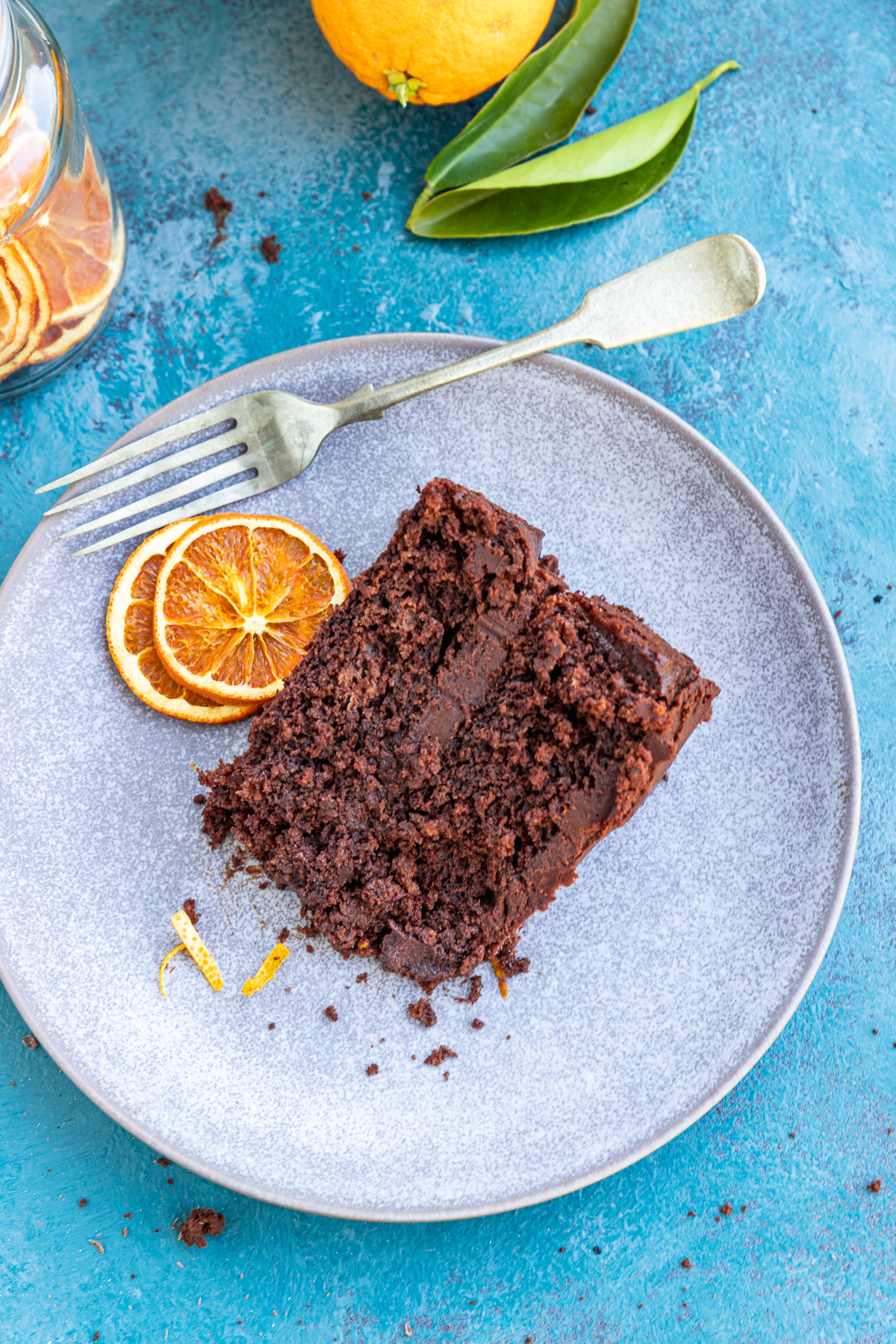 A slice of chocolate orange cake on a pale grey plate with 2 slices of dried orange on the side and a fork - all on a blue background with more orange slices in the corner