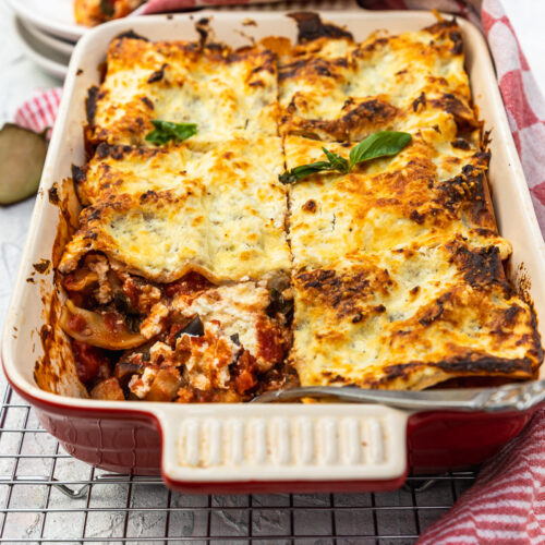 A red baking dish of eggplant lasagna with a piece missing on a cooking rack and with a red checked tea towel in the foreground