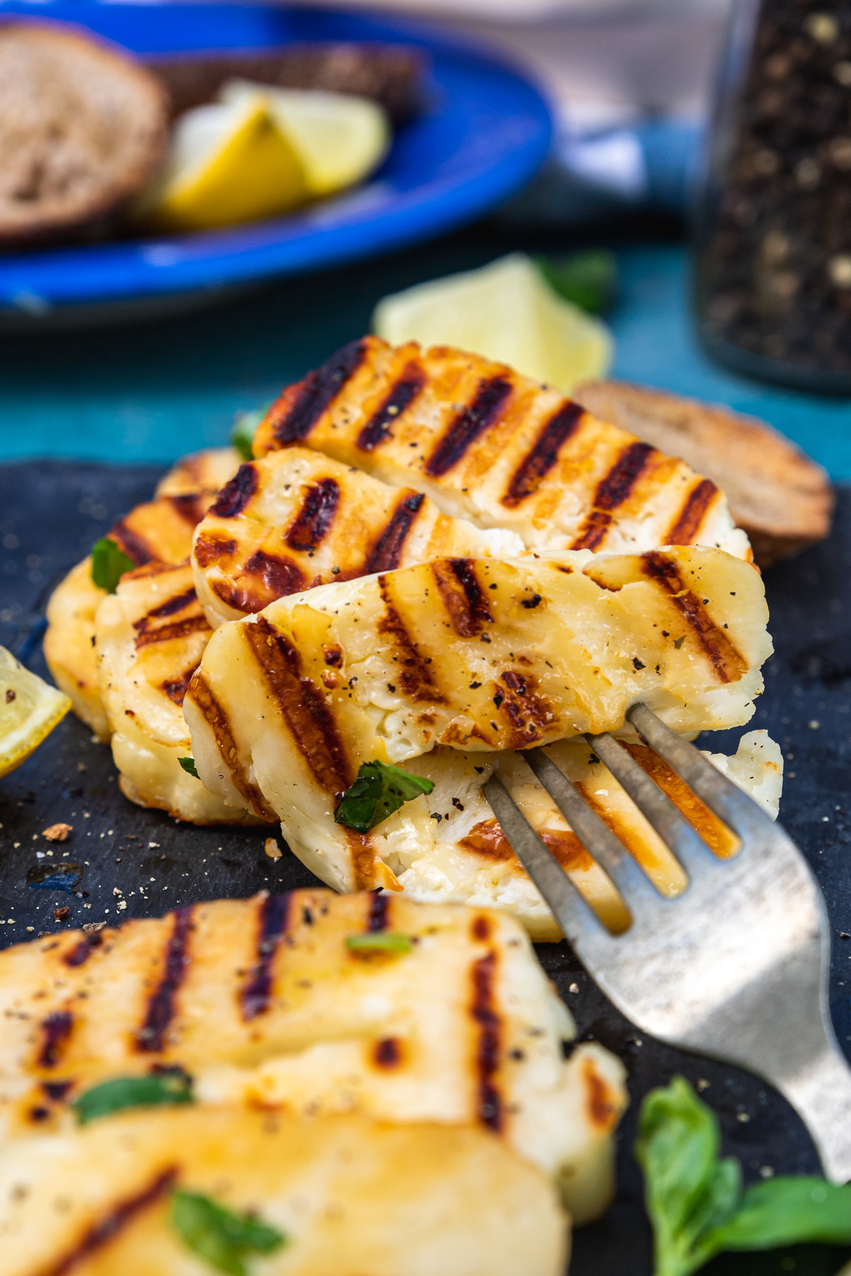 Closeup of someone grabbing a piece of grilled halloumi with a fork from a black platter with more in the background