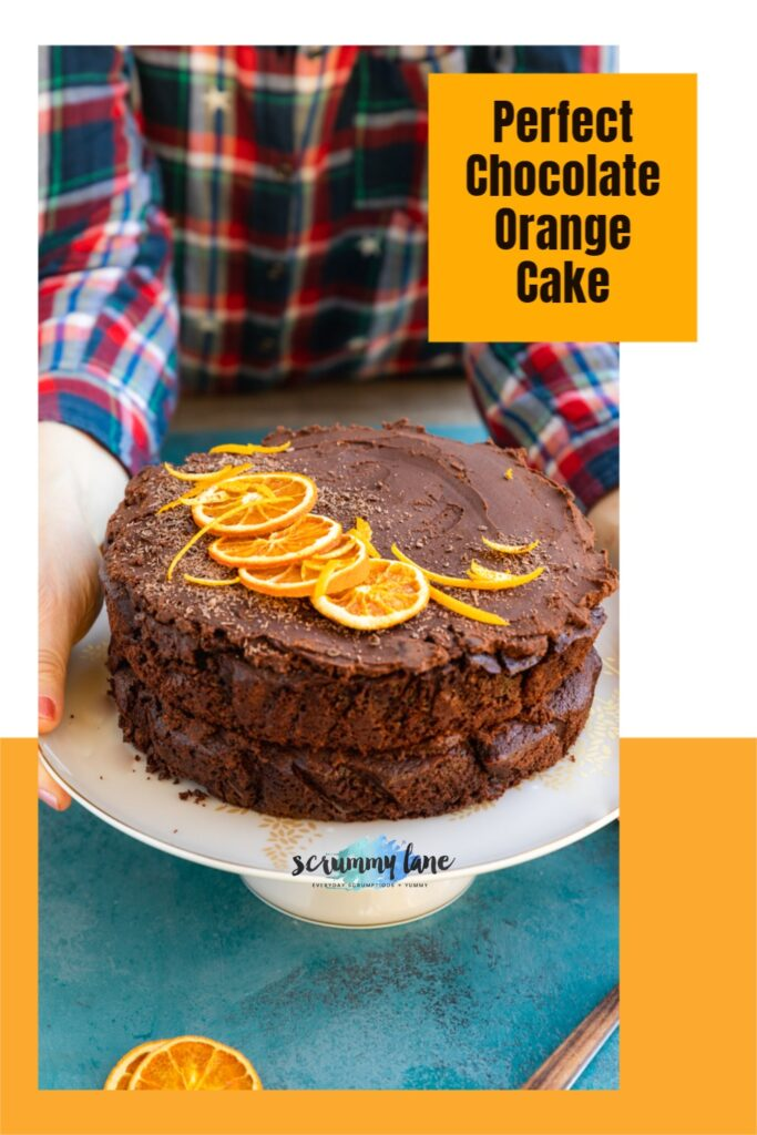 Someone in a checked shirt placing a chocolate orange cake on a white cake stand on a blue table - with title on it for Pinterest