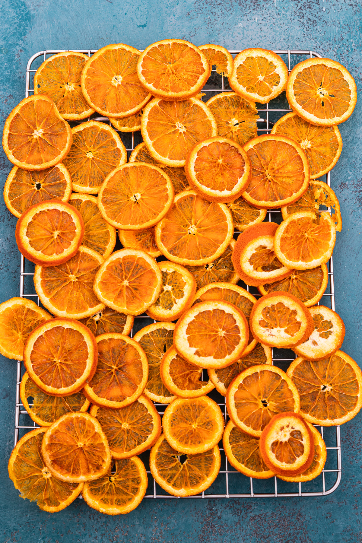Dried orange slices from above piled onto a wire rack and on a blue background