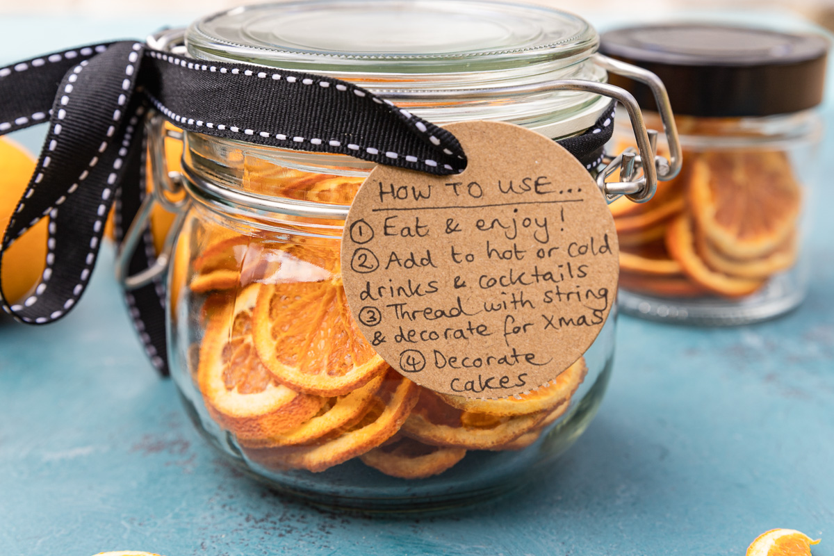 A jar of dried oranges on a blue background and with a black ribbon around the top and a brown label with ways to use the oranges on