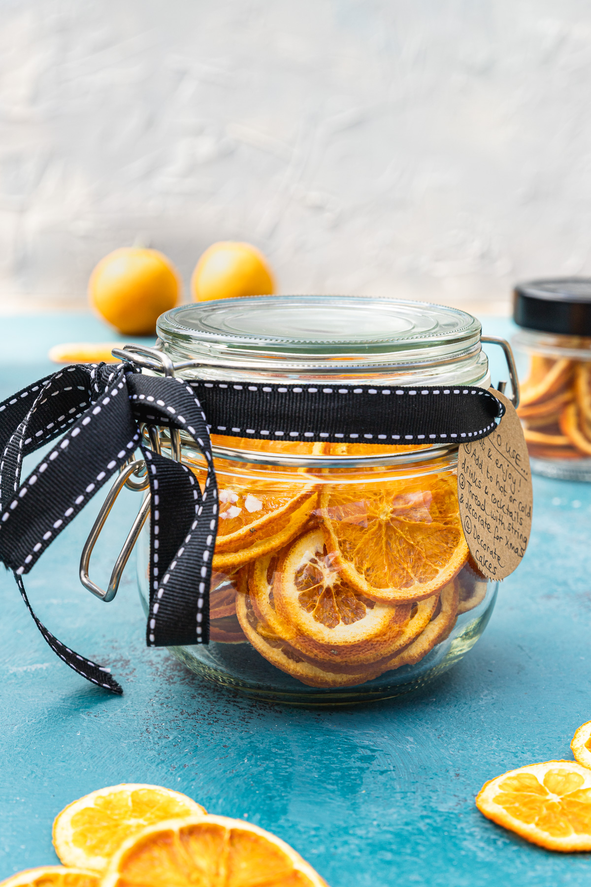 A mason jar full of dried orange slices with a black bow around it and brown label on a blue table top and with oranges and a white wall in the background